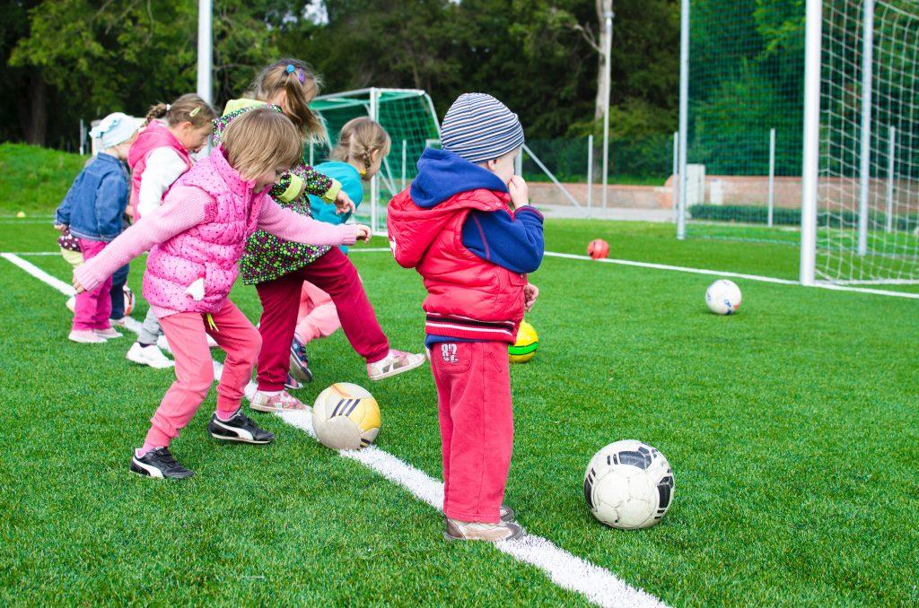 kinderen met voetballen op voetbalveld